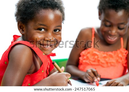 Close up portrait of cute African kid at table holding crayon with friend in background. - stock photo