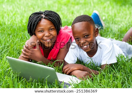 Close up portrait of cute African kids laying on grass with laptop. - stock photo