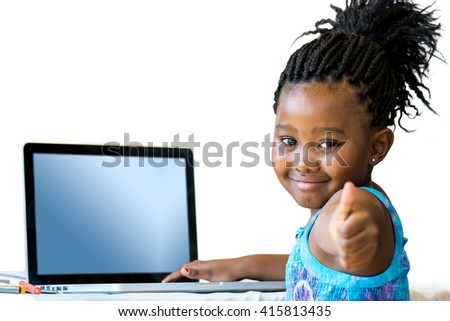 Close up portrait of cute african student with laptop doing thumbs up at desk.Isolated on white background. - stock photo