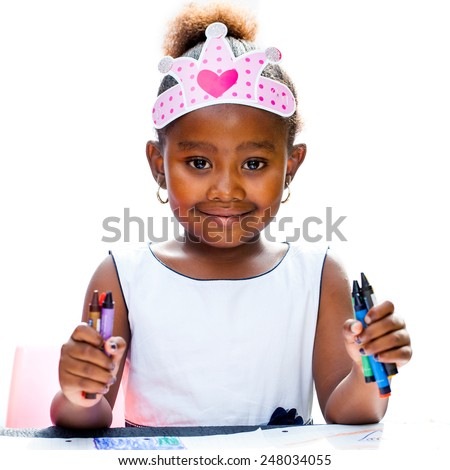 Close up Portrait of Cute Afro girl holding wax crayons.Isolated against white background.
