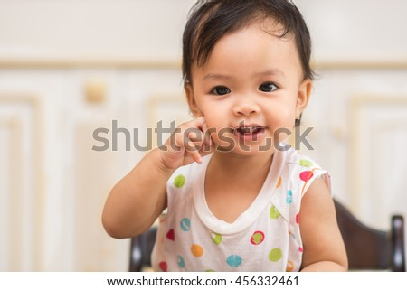 Close up portrait of cute baby girl  on  background, adorable child having fun, happiness concept