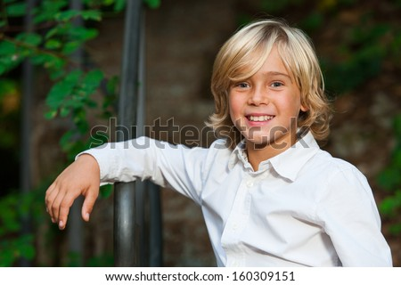 Close up portrait of cute blond boy outdoors.