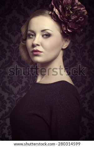 close-up portrait of cute blonde lady with blue dress and spring hair-style. Posing with serious expression, elegant hairdo, cute make-up and big purple flower on head  - stock photo