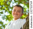 Close up portrait of cute boy in tree. - stock photo