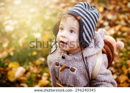 Close-up Portrait of Cute Curious Toddler Boy in Knitted Stripy Hat Looking Up. Image Toned. - stock photo