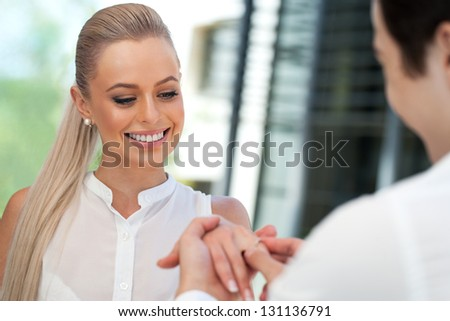 Close up portrait of cute girl being surprised with diamond ring on date. - stock photo