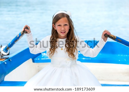 Close up portrait of cute girl in communion dress rowing a boat on river. - stock photo