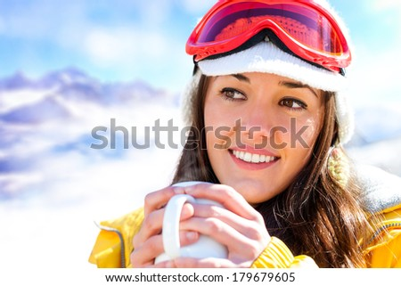 Close up portrait of cute girl in ski wear drinking coffee outdoors. - stock photo