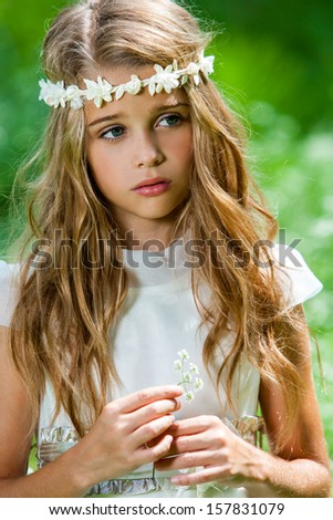 Close up portrait of cute girl in white dress holding flower outdoors. - stock photo