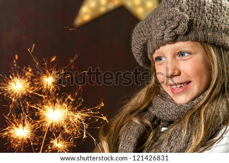 Close up portrait of cute girl looking at festive fire sparks. - stock photo