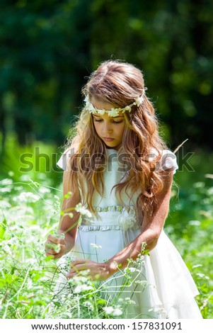 Close up portrait of cute girl picking flowers in field. - stock photo