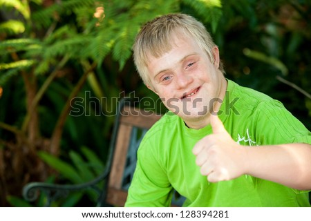 Close up portrait of cute handicapped boy showing thumbs up outside. - stock photo