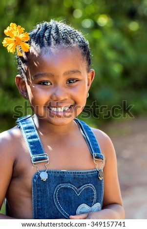 Close up portrait of cute little african child with braids and orange flower in hair.Girl standing outdoors against green background.