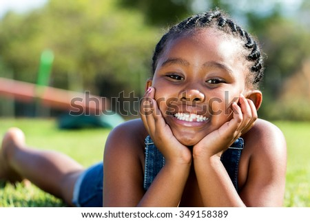Close up portrait of cute little African girl laying with face on hands in park.