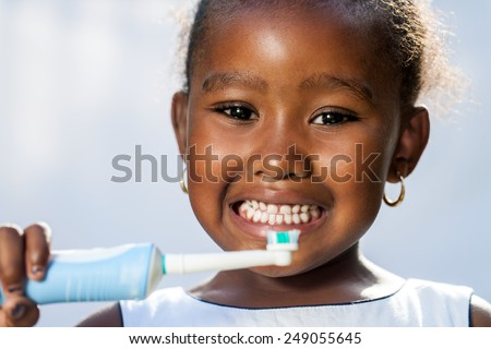 Close up portrait of cute little Afro girl holding electric toothbrush ready to brush teeth. - stock photo
