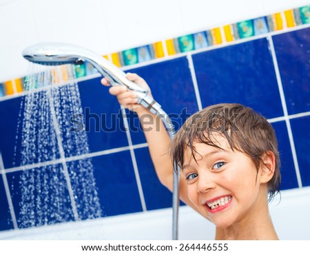 Close-up portrait of cute little boy in bathroom with shower - stock photo