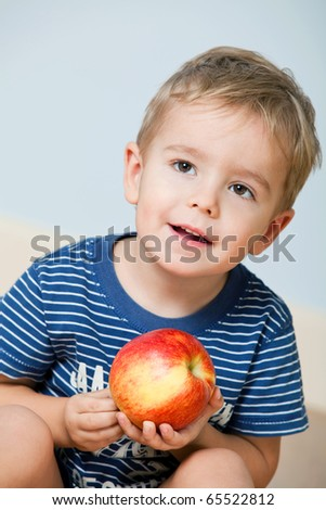 Close up portrait of cute little boy with red apple indoors - stock photo