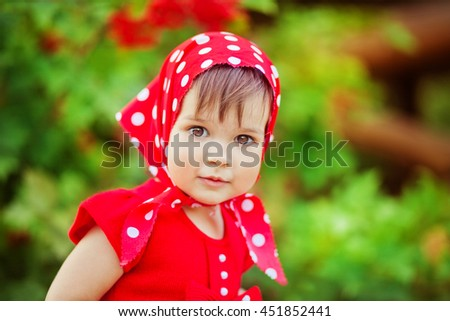 Close up portrait of cute little girl in red dress and head scarf.Colorful photo of pretty child.Lovely kid looking at camera and smiling.  - stock photo