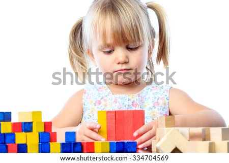 Close up portrait of cute little girl playing with wooden blocks.Isolated on white background. - stock photo