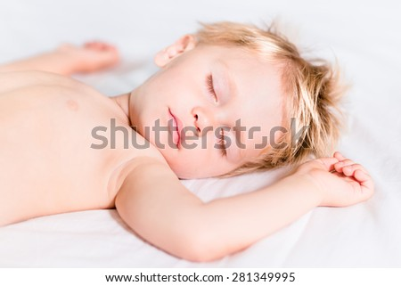 Close-up portrait of cute little kid with blond hair sleeping on white bed. Carefree childhood concept