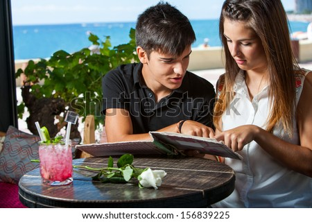 close up portrait of cute teen couple looking at menu in restaurant. - stock photo