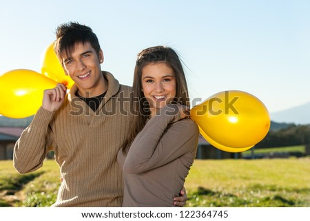 Close up portrait of cute teen couple outdoors with yellow balloons. - stock photo