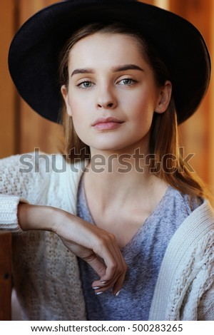 Close up portrait of cute teenage girl in a hat in country style in wooden house