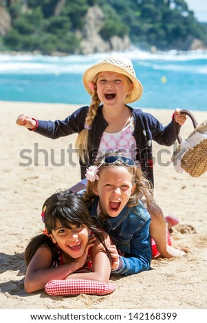Close up portrait of cute threesome making human pile on beach. - stock photo