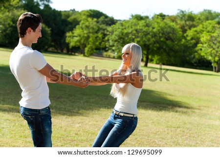 Close up portrait of cute young couple holding hands in park. - stock photo