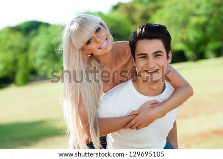 Close up portrait of cute young couple piggybacking outside. - stock photo