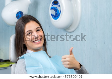Close up portrait of cute young woman doing thumbs up at appointment in dental clinic.
