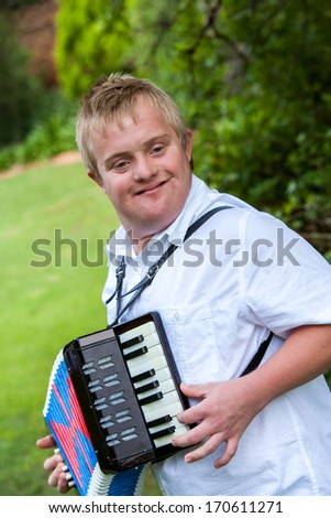 Close up portrait of disabled boy playing the accordion outdoors. - stock photo