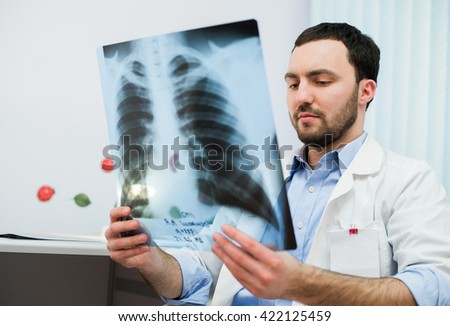 close up portrait of doctor looking at chest x ray in his office - stock photo