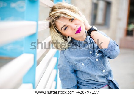 Close-up portrait of dreamy smiling blond girl with flying short hair and bright pink lips wearing blue denim shirt leaning on blue and white stripes fence on the background and playing with her hair - stock photo