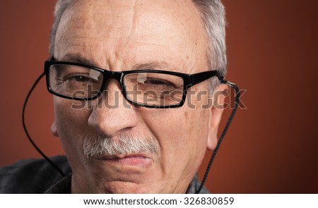 Close-up portrait of elderly man in glasses with a grimace of pain - stock photo