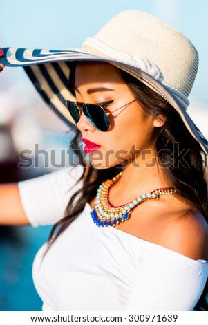 Close up  portrait of elegant glamour  asian girl in stylish  sunglasses posing in yacht club wearing straw hat, bright make up, hight crop top and jeans skirt , summer vacation mood. - stock photo