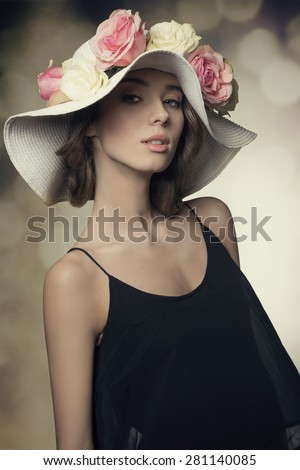close-up portrait of elegant spring brunette woman with black dress and big hat with colorful flowers. Looking in camera, fashion pose  - stock photo