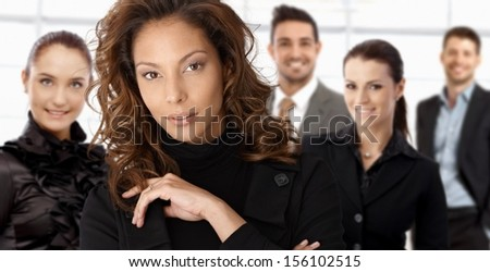 Close-up portrait of elegant young businesswoman with colleagues at background.