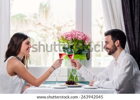 Close up portrait of elegant young couple having romantic dinner in restaurant. Couple sitting next to window with colorful flower bouquet and making a toast with rose wine.