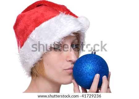Close up portrait of emotional girl in santa claus hat playing with decoration balls