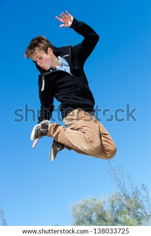 Close up portrait of energetic boy jumping outdoors. - stock photo