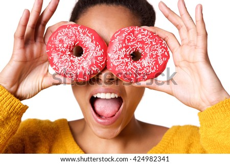 Close up portrait of excited young african woman holding colorful donuts against her eyes - stock photo