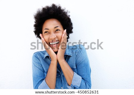 Close up portrait of excited young african woman holding face in hands
