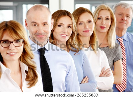 Close-up portrait of executive business people standing in a row at office and looking at the camera. Business persons. - stock photo