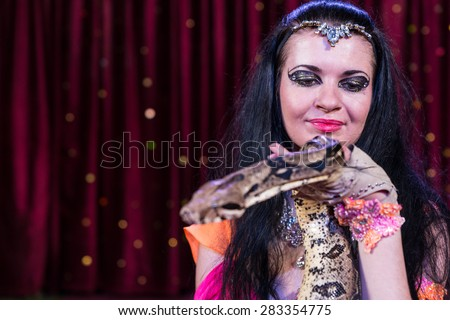Close Up Portrait of Exotic Dark Haired Snake Charmer Holding Large Snake on Stage with Red Curtain in Background and Copy Space - stock photo