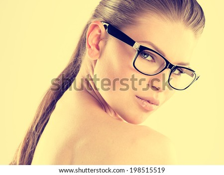 Close-up portrait of fashion pretty girl in spectacles posing in studio. Young beautiful Caucasian female model in eyewear.  - stock photo