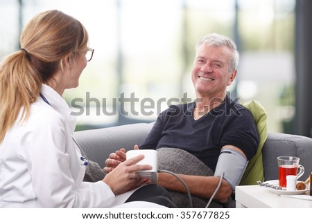 Close-up portrait of female doctor checking the blood pressure of her senior patient while sitting at nursing home. - stock photo