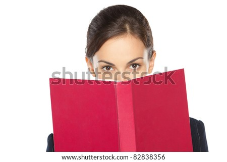 Close-up portrait of female in suit peeking over the book, isolated on white background