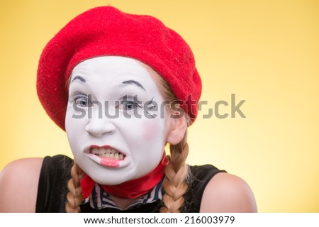 Close-up portrait of female mime with white funny face, red hat and red scarf looking at the camera isolated on yellow background  - stock photo