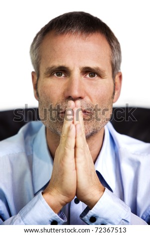 Close up portrait of focused businessman in blue shirt looking straight and folding hands in front of his mouth, isolated on white background.